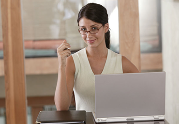Woman wearing glasses and smiling at camera while sitting behind a laptop computer
