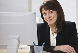 Mature businesswoman smiles from behind her desktop computer in her office at work